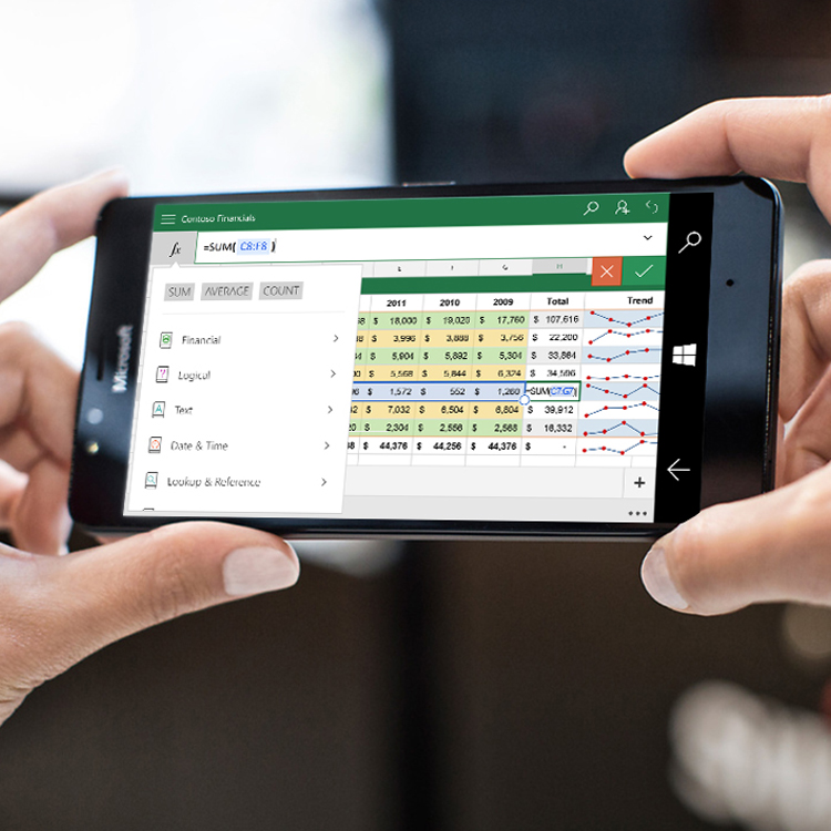 Woman's hands holding up Lumia phone with Excel open on screen