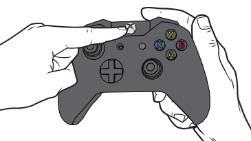 A finger reaches to press the Xbox button on an Xbox One controller.