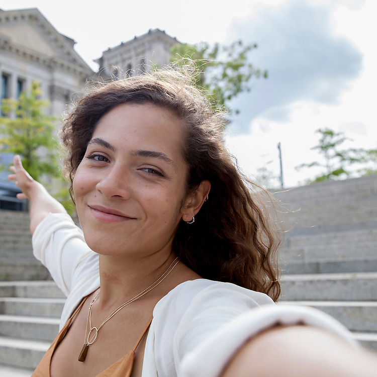Woman standing in from of european stone steps taking a selfie