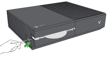 An illustration of a hand inserting the straight end of a paper clip into the eject hole, located next to the orange rectangle on the side of an Xbox One console