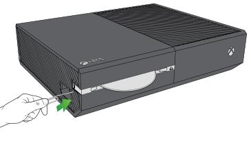 Una ilustración de una mano insertando el extremo recto de un clip en el orificio de expulsión, situado junto al rectángulo naranja en el lateral de una consola Xbox One