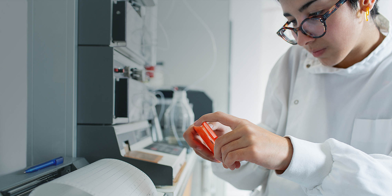 Woman in laboratory wearing lab coat taking a picture with her Lumia 735