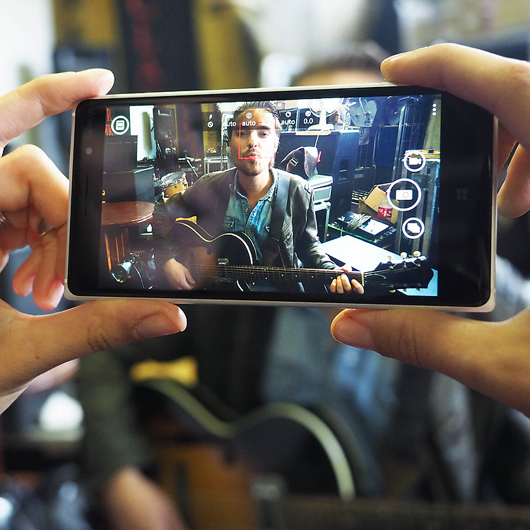 Young woman's hands holding Lumia 830 capturing a live performance of a man with a guitar surrounded by band equipment