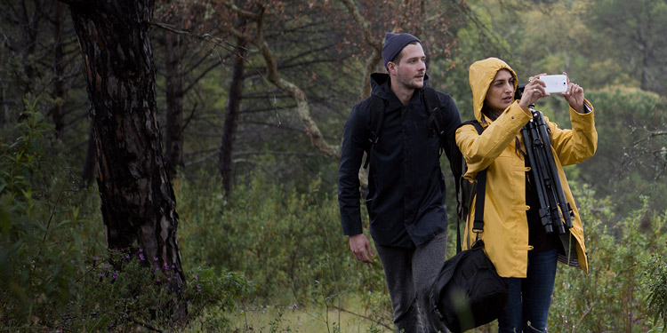 Woman and man wearing rain gear walking through rainy forest, the woman is carrying camera gear and takes a photo with her white Lumia 950