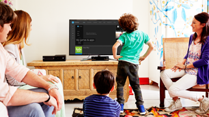 A family gathers in front of an Xbox One console and TV, ready to play.