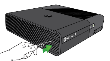 A hand inserts a paper clip bent to have a long arm into the eject hole on the side of an Xbox 360 E console.